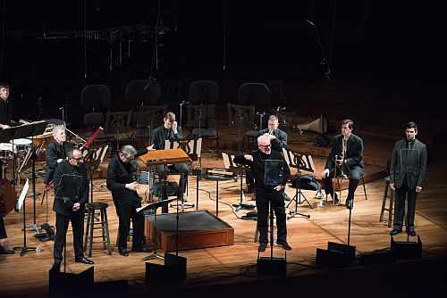 "(Front row, L to R) Narrator Elvis Costello, conductor Michael Tilson Thomas as The King, Malcolm McDowell as the Devil, and Nick Gabriel as the Soldier, with members of the San Francisco Symphony in Stravinsky's ""A Soldier's Tale."" Photo by Kristen Loken."